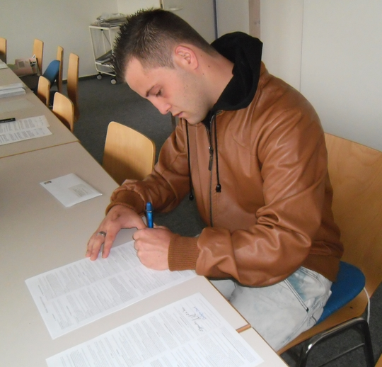 Christopher Oberst unterschreibt seinen Lehrvertrag